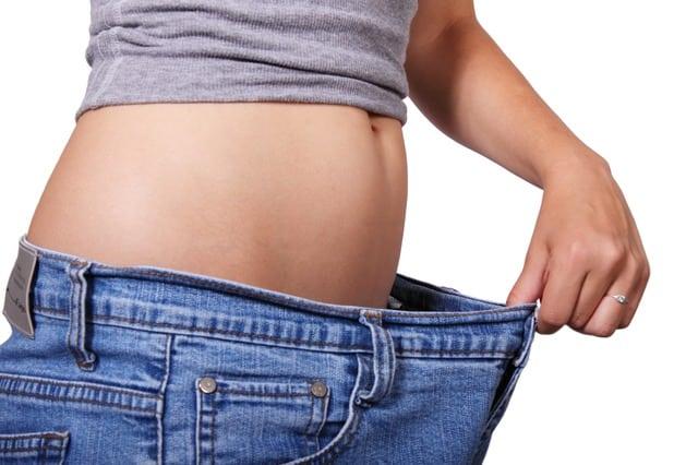 Bauch einer Frau, die eine zu weite Hose trägt