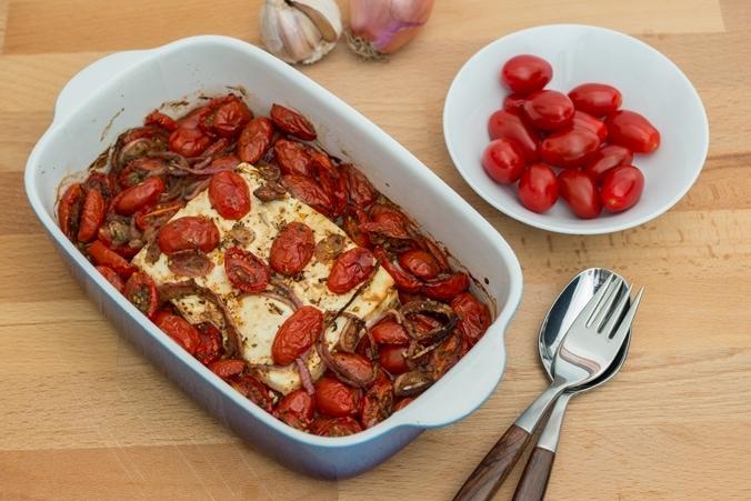 Feta mit Tomaten in einer Auflaufform, daneben Besteck
