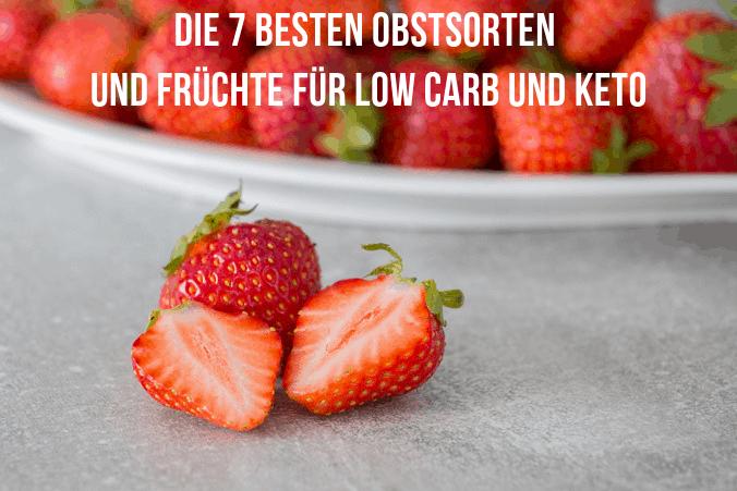 Im Vordergrund eine ganze und eine halbierte Erdbeere, im Hintergrund eine Schale mit vielen Erdbeeren