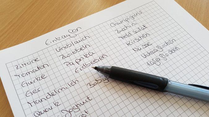 Zettel mit Kuli und Einkaufsliste