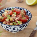 Kichererbsensalat mit Tomaten und Feta, angerichtet, Ansicht von schräg vorne