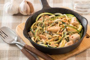 Zucchini-Nudeln mit Erdnuss-Soße in einer Pfanne