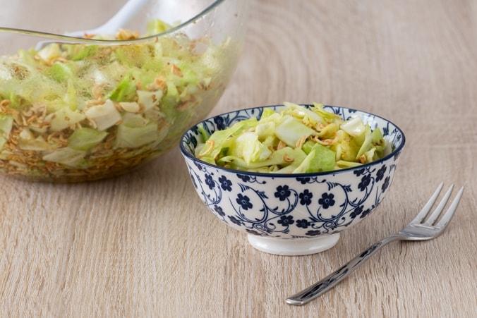Asiatischer Mie-Nudel-Salat im Schälchen angerichtet, große Schüssel im Hintergrund