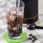Cold Brew Coffee im Glas, Kanne im Hintergrund