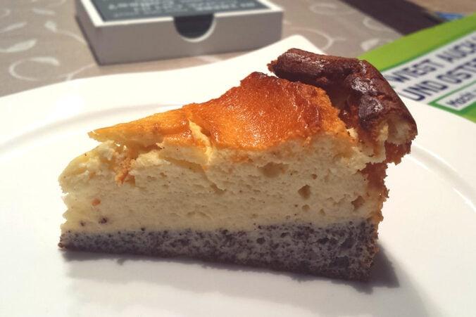 Ein Stück Käsekuchen mit Mohn-Boden auf deinem Teller
