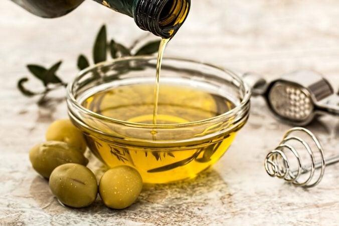 Olivenöl wird in ein Schälchen gegossen, daneben liegen ein paar Oliven