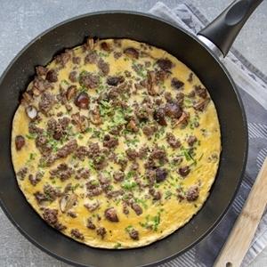 Pilz-Omelette mit Hackfleisch in einer Pfanne