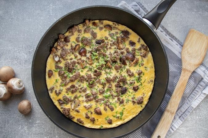 Omelette mit Champignons und Hackfleisch in einer Pfanne