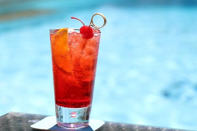 Roter Cocktail im Glas, im Hintergrund ein Pool