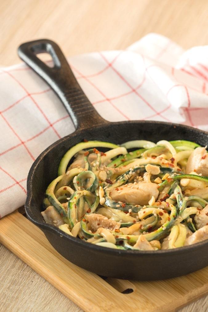 Zucchini-Nudeln mit Erdnuss-Chili-Soße in einer Pfanne, mit einem weiß-roten Küchentuch dahinter